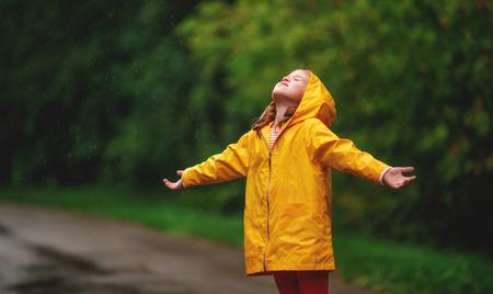 the happy child girl enjoying autumn rain 版權商用圖片