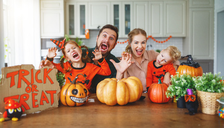 happy Halloween! family mother father and children cut a pumpkin for holiday home Stock Photo