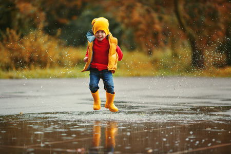 happy child baby boy with rubber boots jump in puddle on an autumn walk Stok Fotoğraf - 109617458