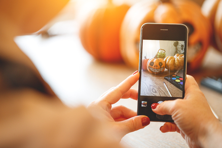 a woman artist prepares for halloween and photographed on smartphone his work painted pumpkin Banco de Imagens