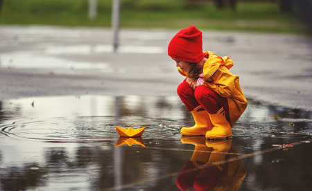 happy child girl with umbrella and paper boat in a puddle in   autumn on nature Stock Photo