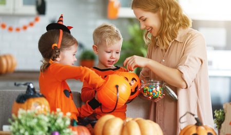happy Halloween! a mother treats children with candy at home 스톡 콘텐츠