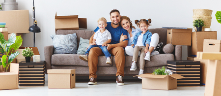 happy family mother father and children move to a new apartment and unpack boxes Imagens