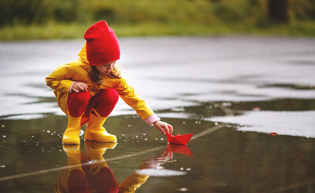 happy child girl with paper boat in a puddle in  autumn on nature Stock Photo