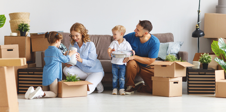 happy family mother father and children move to a new apartment and unpack boxes Archivio Fotografico