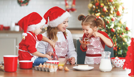 happy funny mother and children  bake christmas cookies Imagens