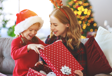 happy family mother and child daughter  open presents on Christmas morning