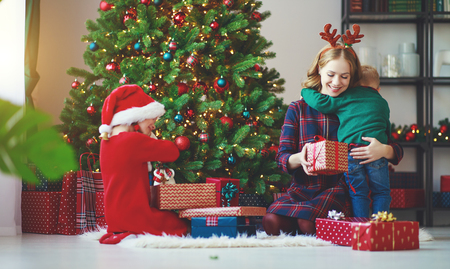 happy family mother and children open presents on Christmas morning