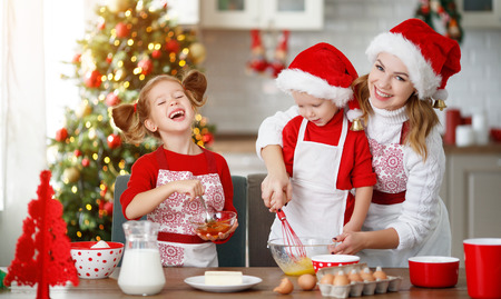 happy funny mother and children  bake christmas cookies Stock Photo