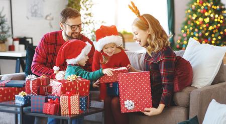 Familia feliz, padres e hijos abren regalos en la mañana de Navidad