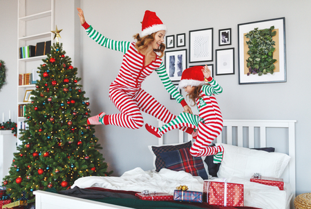happy family mother and child daughter  in pajamas  jumping  in bed on on christmas morning