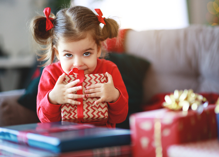 happy child girl with christmas gifts near christmas tree in morning Foto de archivo