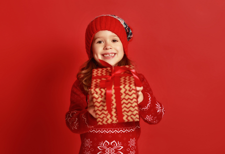 happy child girl with christmas gift over red background Stockfoto