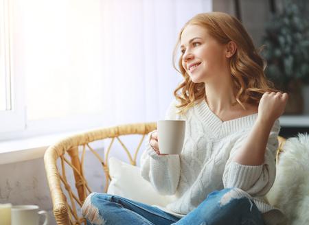 heureuse jeune femme buvant du café du matin par la fenêtre en hiver