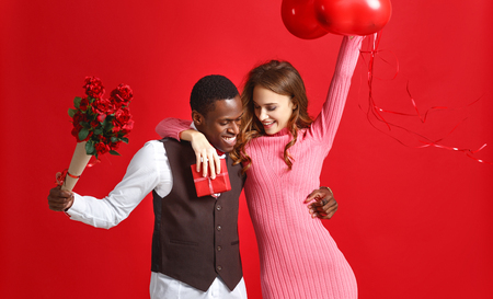 valentines day concept. happy young couple with heart, flowers, gift on red background