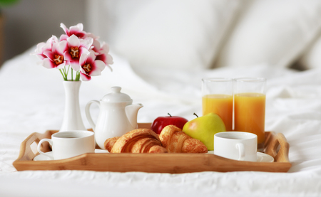 breakfast in bed of coffee, croissants, orange juice and fruit on a tray Stock Photo