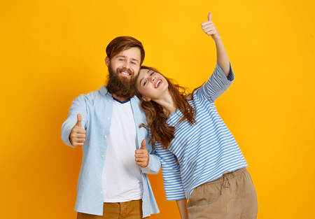 couple of young emotional people man and woman on yellow background