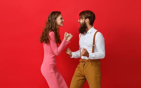 Feliz pareja ganó emocionalmente celebrando la victoria sobre fondo rojo de color