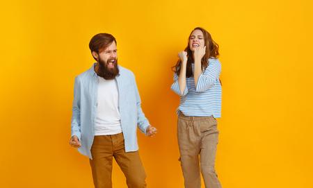 happy couple won emotionally celebrating win on colored yellow background