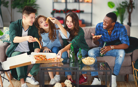 group of happy young  friends with beer and pizza at home Фото со стока