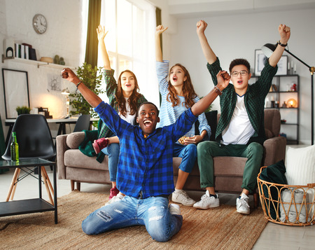 group of happy young  friends fans watching a match on tv with beer and pizza at home