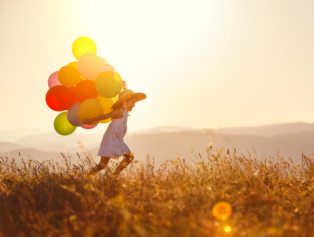young happy child girl with balloons at sunset in summer Foto de archivo