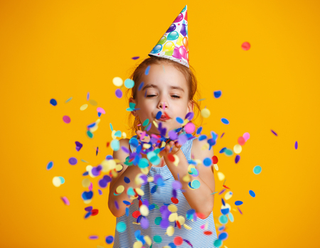 happy birthday child girl with confetti on  colored yellow background Archivio Fotografico