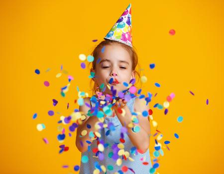 Feliz cumpleaños niña niña con confeti sobre fondo amarillo de color Foto de archivo