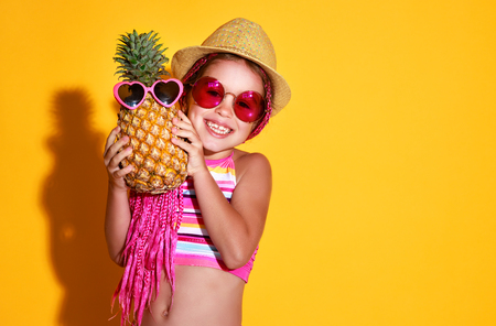 Funny happy child girl in swimsuit, pink glasses and hat with pineapple is laughing on  color yellow background Stock Photo - 116644105
