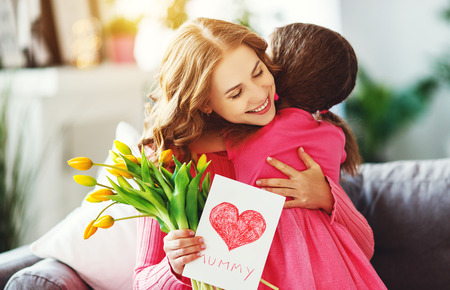 happy mothers day! child daughter congratulates mother and gives a bouquet of flowers to tulips and postcard
