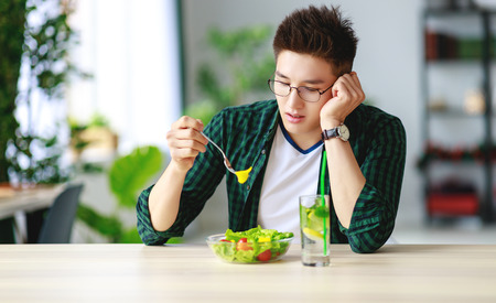 healthy eating. happy young man eating salad in the morning in kitchen Banco de Imagens