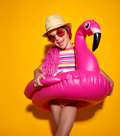 happy child girl in swimsuit with swimming ring flamingo on a colored yellow background