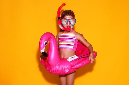 gelukkig kindmeisje in zwempak met zwemmende ringflamingo op een gekleurde gele achtergrond