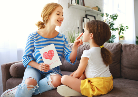Happy mothers day! Child daughter congratulates moms and gives her a postcard