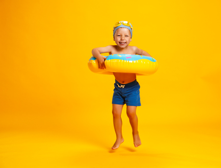 happy child boy in swimsuit with swimming ring donut on a colored yellow background