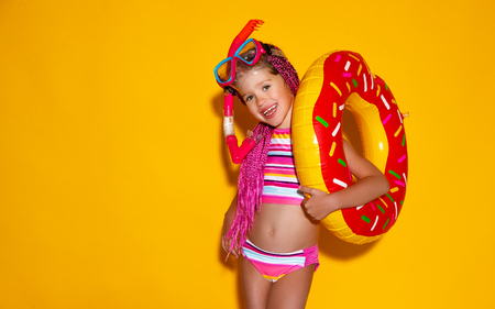 happy child girl in swimsuit with swimming ring donut on a colored yellow background Standard-Bild