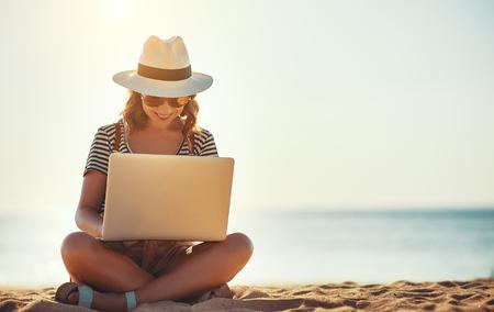 Mujer joven que trabaja con un portátil en la naturaleza en la playa de verano