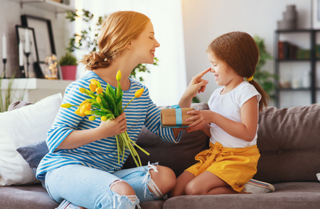 happy mothers day! child daughter congratulates mother and gives a bouquet of flowers to tulip and gift