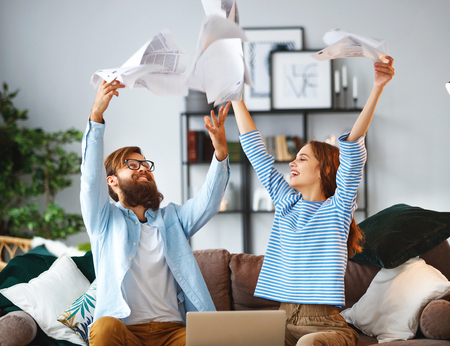 married couple with bills receipts documents and a laptop at home