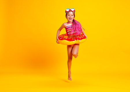 happy child girl in swimsuit with swimming ring donut on a colored yellow background 免版税图像
