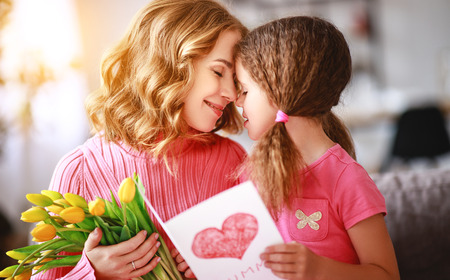 happy mothers day! child daughter congratulates mother and gives a bouquet of flowers and postcard
