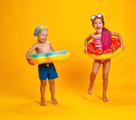 happy children girl and boy in swimsuit with swimming ring donut on a colored yellow background