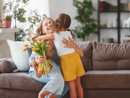 Happy mothers day! Children congratulates moms and gives her a gift and flowers tulips Banco de Imagens
