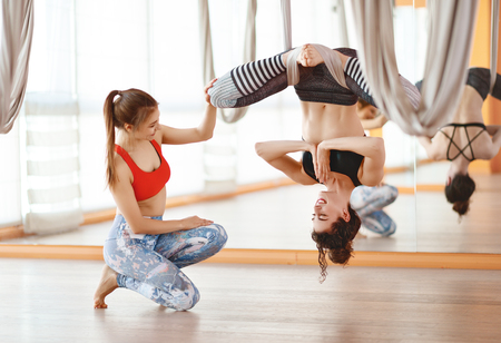 a group of people engaged in a class of yoga Aero in hammocks antigravity
