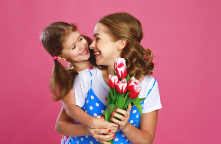 happy mothers day! child daughter congratulates mother and gives a bouquet of flowers color pink background