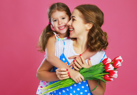 Happy mothers day! child daughter congratulates mother and gives a bouquet of flowers color pink background Stock Photo