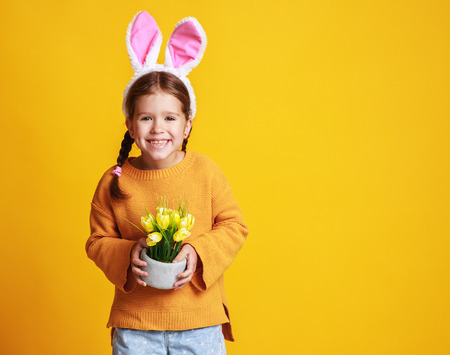 Funny happy child girl with Easter  bunny ears and with spring flowers tulips on yellow background Zdjęcie Seryjne