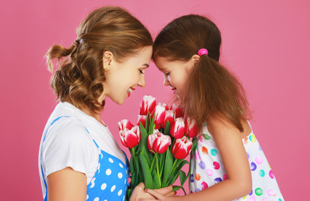 Happy mothers day! child daughter congratulates mother and gives a bouquet of flowers color pink background Banco de Imagens