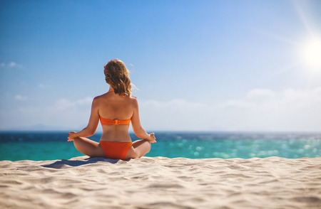 Woman practices yoga and meditates in the lotus position on the beach Stock fotó - 119249986