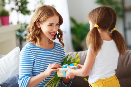 Happy mother's day! child daughter congratulates mother and gives a bouquet of flowers to tulip and gift